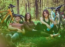 Groupe de jeunes amis trimardant par la forêt avec des vélos sur a Images libres de droits