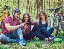Groupe de jeunes amis trimardant par la forêt avec des vélos sur a Photos libres de droits