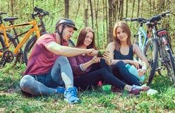 Groupe de jeunes amis trimardant par la forêt avec des vélos sur a Photo libre de droits