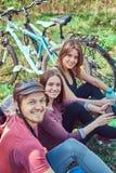 Groupe de jeunes amis trimardant par la forêt avec des vélos sur a Photos stock