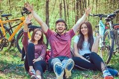 Groupe de jeunes amis trimardant par la forêt avec des vélos sur a Photographie stock libre de droits