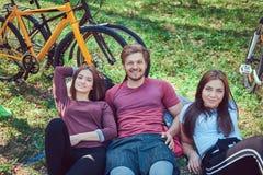 Groupe de jeunes amis trimardant par la forêt avec des vélos sur a Photographie stock