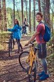 Groupe de jeunes amis trimardant par la forêt avec des vélos un beau jour d'été Photos libres de droits
