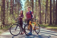 Groupe de jeunes amis trimardant par la forêt avec des vélos un beau jour d'été Image libre de droits
