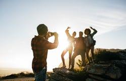 Groupe de jeunes amis trimardant sur la montagne Photos libres de droits