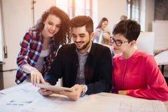 Groupe de jeunes architectes travaillant sur l'ordinateur portable Photo stock