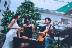 Groupe de jeunes asiatiques heureux tout en appréciant la partie de nuit et Image libre de droits