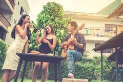 Groupe de jeunes asiatiques heureux tout en appréciant la réception en plein air Photographie stock libre de droits