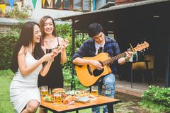 Groupe de jeunes asiatiques heureux tout en appréciant la réception en plein air Photos libres de droits