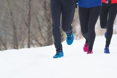 Groupe de jeunes athlètes courant sur la neige, foyer sur ses pieds Photo libre de droits