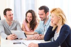 Groupe de 4 jeunes attirants travaillant sur un ordinateur portable images libres de droits