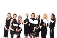 Groupe de jeunes belles femmes dans la robe noire d'isolement sur le fond blanc photographie stock