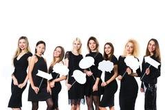 Groupe de jeunes belles femmes dans la robe noire d'isolement sur le fond blanc photo libre de droits