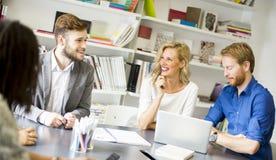 Groupe de jeunes collègues s'asseyant sur le bureau moderne Image libre de droits