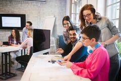 Groupe de jeunes concepteurs regardant le comprimé numérique Photos libres de droits