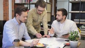 Groupe de jeunes concepteurs travaillant à un comprimé de dessin banque de vidéos