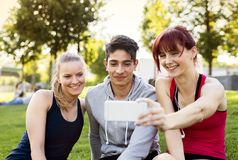 Groupe de jeunes coureurs avec un smartphone en parc Photographie stock libre de droits
