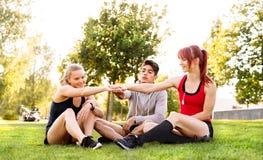 Groupe de jeunes coureurs s'asseyant sur l'herbe empilant des mains Photos stock