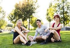 Groupe de jeunes coureurs se reposant en parc Image stock
