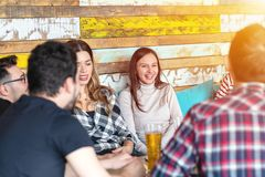 Groupe de jeunes d'amis s'asseyant dans une barre souriant et ayant l'amusement buvant ensemble de la bière photographie stock
