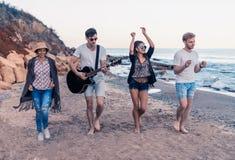 Groupe de jeunes et gais amis marchant sur la plage Photographie stock