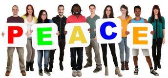 Groupe de jeunes ethniques multi tenant la paix de mot Images stock