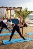 Groupe de jeunes femelles pratiquant le yoga sur le bord de la mer pendant le lever de soleil Photo libre de droits