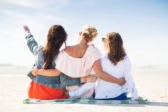 Groupe de jeunes femmes étreignant sur la plage Image libre de droits