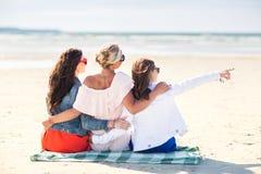 Groupe de jeunes femmes étreignant sur la plage Photographie stock
