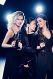 Groupe de jeunes femmes célébrant et buvant du champagne ensemble Photographie stock