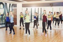 Groupe de jeunes femmes dans la classe de forme physique, aérobic photos stock