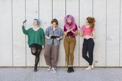 Groupe de jeunes femmes de diversité employant la technologie d'isolement contre Images libres de droits