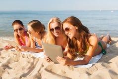Groupe de jeunes femmes de sourire avec des comprimés sur la plage Image stock