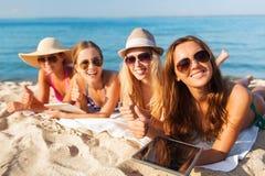 Groupe de jeunes femmes de sourire avec des comprimés sur la plage Photos stock