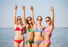 Groupe de jeunes femmes de sourire buvant sur la plage Photographie stock