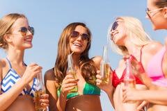 Groupe de jeunes femmes de sourire buvant sur la plage Photo stock
