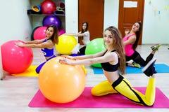 Groupe de jeunes femmes faisant des exercices avec des fitballs dans une forme physique Photos libres de droits