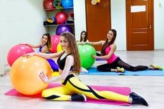 Groupe de jeunes femmes faisant des exercices avec des fitballs dans une forme physique Photo stock