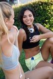 Groupe de jeunes femmes faisant s'étirant en parc Photographie stock