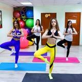 Groupe de jeunes femmes méditant se tenant après la formation dans le fitne Photos libres de droits
