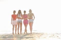 Groupe de jeunes femmes marchant sur la plage Photographie stock