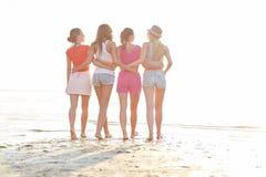Groupe de jeunes femmes marchant sur la plage Images stock