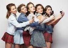 Groupe de jeunes femmes regardant leurs smartphones Image libre de droits