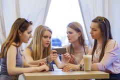 Groupe de jeunes femmes s'asseyant autour du Tableau mangeant le dessert Image stock