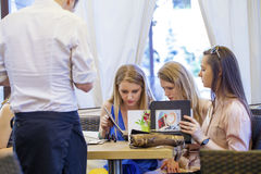 Groupe de jeunes femmes s'asseyant autour du Tableau mangeant le dessert Image libre de droits