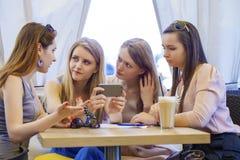 Groupe de jeunes femmes s'asseyant autour du Tableau mangeant le dessert Photo libre de droits