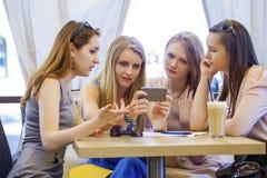 Groupe de jeunes femmes s'asseyant autour du Tableau mangeant le dessert Images libres de droits