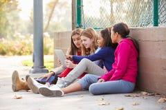 Groupe de jeunes filles à l'aide de la Tablette de Digital dans le parc Photos stock