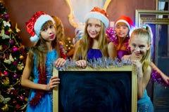 Groupe de jeunes filles célébrant Noël Panneau noir Photographie stock libre de droits