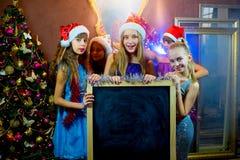 Groupe de jeunes filles célébrant Noël Panneau noir Image stock